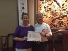 Maître Yan remet le diplome de Qi Gong de professeur de Qi Gong forme yi Jing Jin en août 2015.